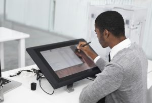 A young man working on a large touchscreen